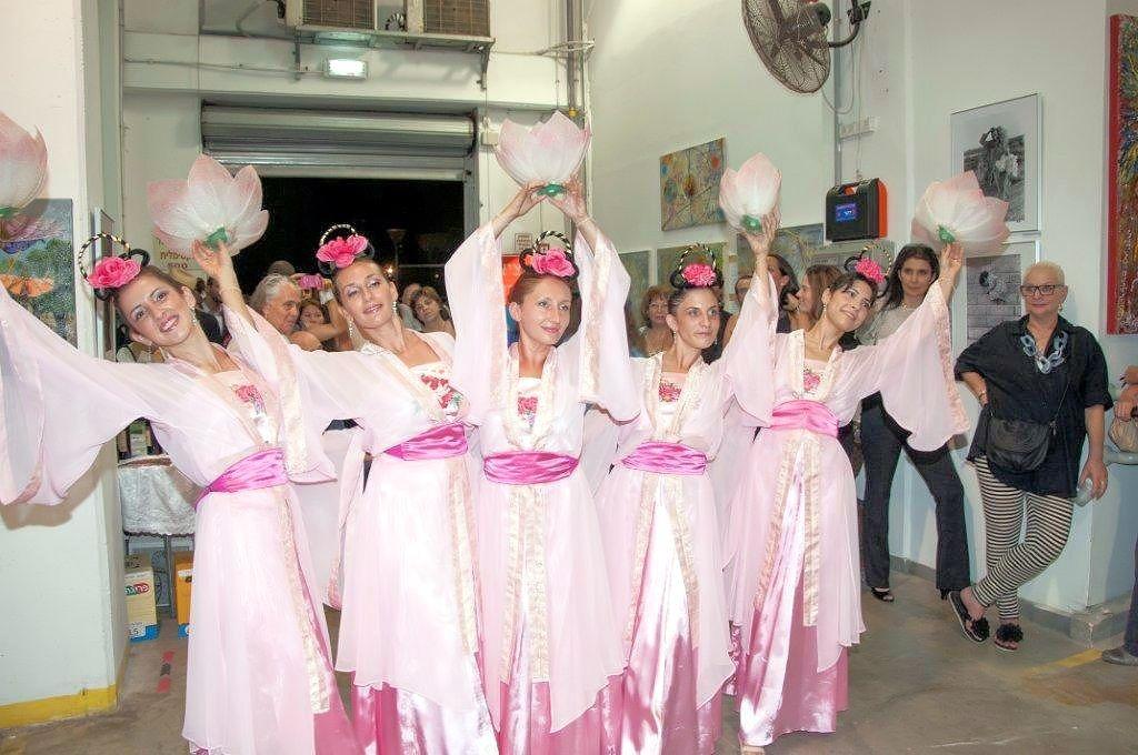 На выставке фотографий, девушки в розовых одеждах исполнили традиционные китайские танцы, чтобы показать зрителям красоту этой духовной практики.